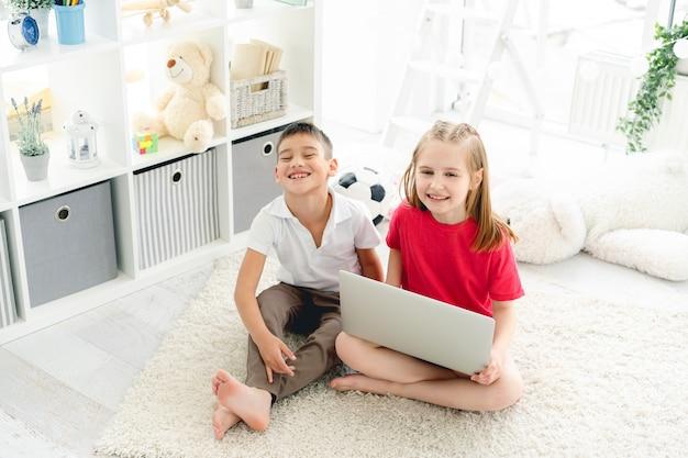 Piccoli amici sorridenti con il computer portatile