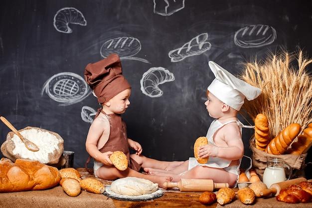 Piccoli bambini affascinanti in grembiuli sulla tavola con pane
