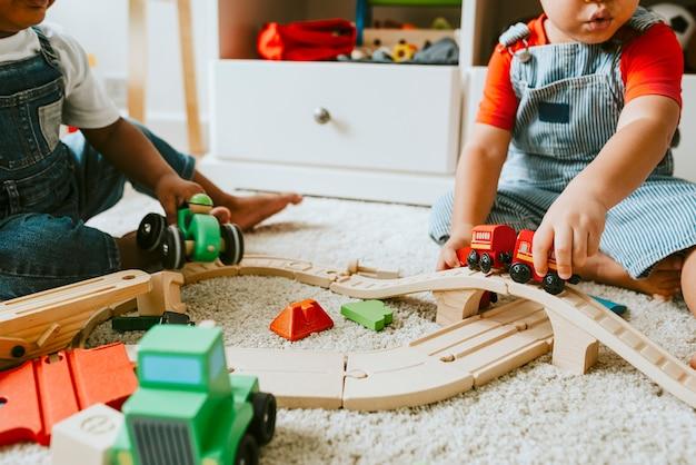 Piccoli bambini che giocano con un giocattolo del treno ferroviario