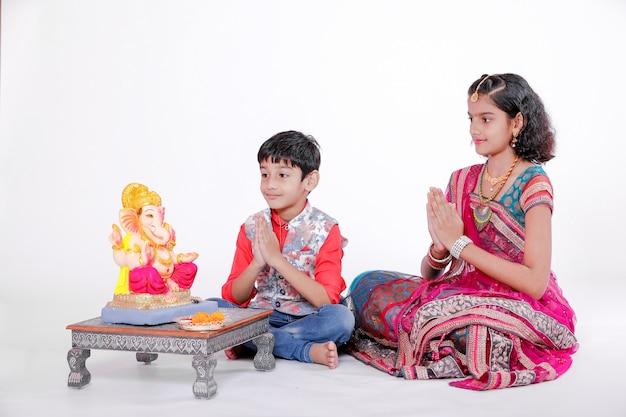 Piccoli bambini indiani con lord ganesha e pregando, festival indiano di ganesh