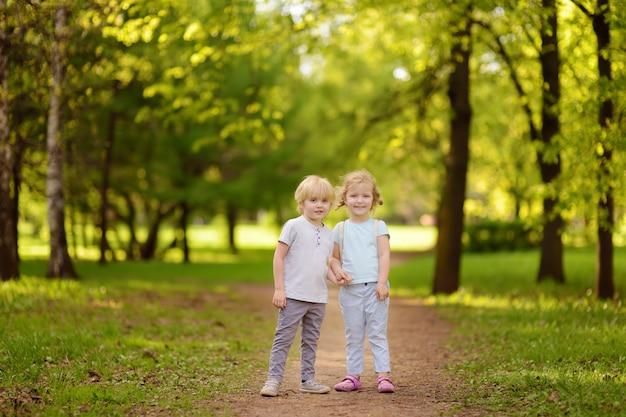 Piccoli bambini svegli che giocano insieme e che si tengono per mano in soleggiato