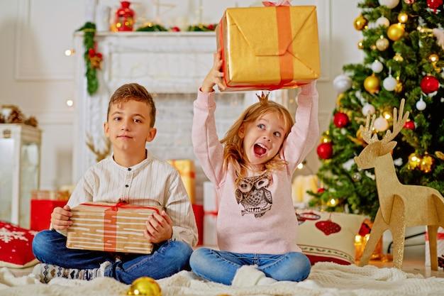 Piccoli bambini svegli con i regali di natale a casa