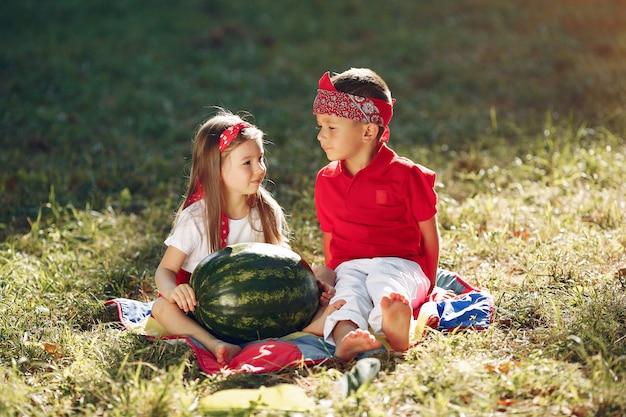 Piccoli bambini svegli con le angurie in un parco