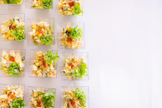 Piccoli bicchieri con insalate fresche, uova, salmone e cetrioli in piedi sul tavolo bianco