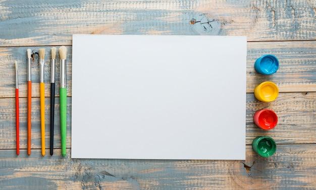 Piccoli contenitori e pennelli per acquerello con lenzuolo bianco