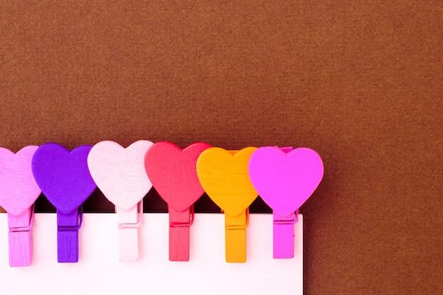 Piccoli cuori colorati tengono una nota di carta. il concetto di una nota per il giorno di san valentino