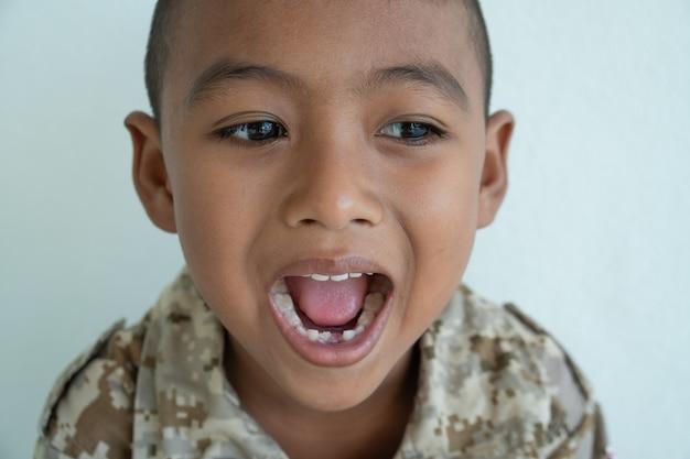 Piccoli denti asiatici svegli di sorriso e di manifestazione del ragazzo rotti