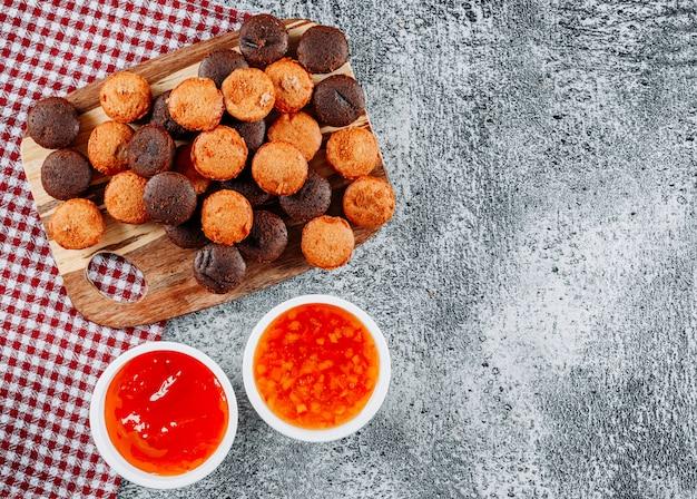 Piccoli dolci di vista superiore nel tagliere con gelatina in ciotole sul panno di picnic e strutturato leggero
