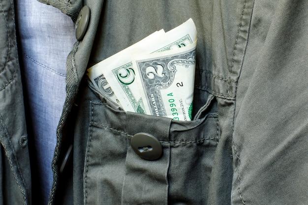 Piccoli dollari nella tasca di una giacca da lavoro verde. il concetto di guadagnare, risparmiare o spendere soldi. concetto monetario