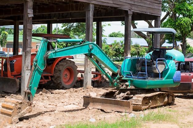 Piccoli escavatori verdi che lavorano nell'area di costruzione