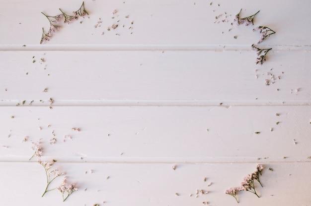 Piccoli fiori che formano un cerchio su un tavolo di legno