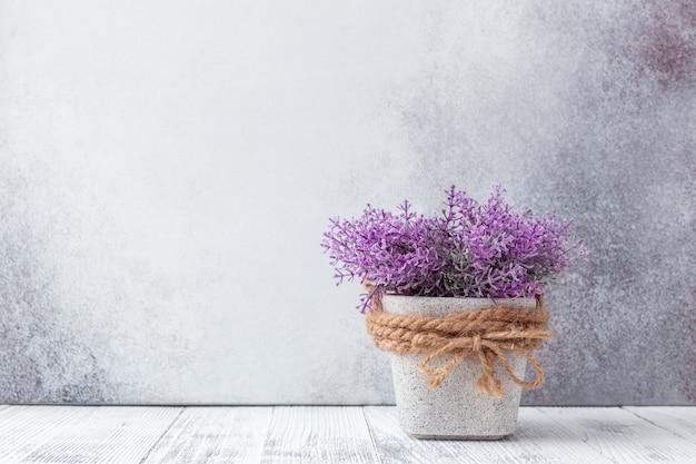 Piccoli fiori viola in vasi di ceramica grigi su sfondo di pietra stile rustico