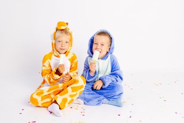 Piccoli fratelli in costumi divertenti seduto su uno sfondo bianco