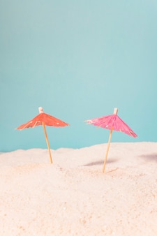Piccoli ombrelli per bevande nella sabbia