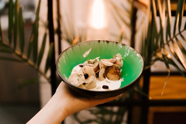 Piccoli pancake in un piatto con le bacche e la panna acida casalinga, dessert in un caffè, menu dei bambini, fuoco selettivo