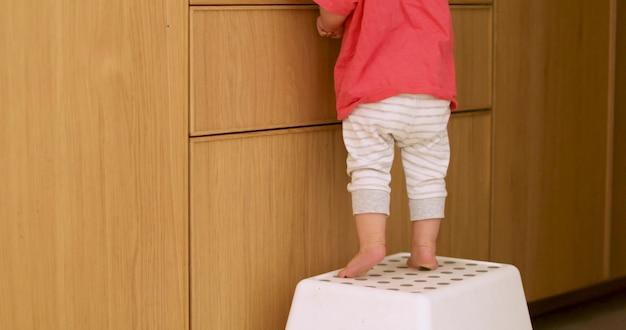 Piccoli piedi del bambino sulla sedia della cucina in legno in stile rustico