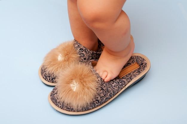 Piccoli piedini paffuti nelle pantofole della mamma