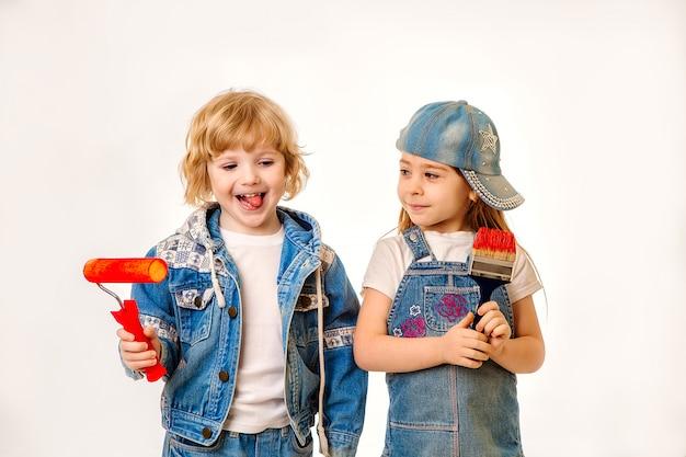Piccoli pittori coppia innamorata, bambini, un ragazzo e adorabile ragazza in giacca di jeans. nelle mani di un pennello e rullo con vernice rossa.