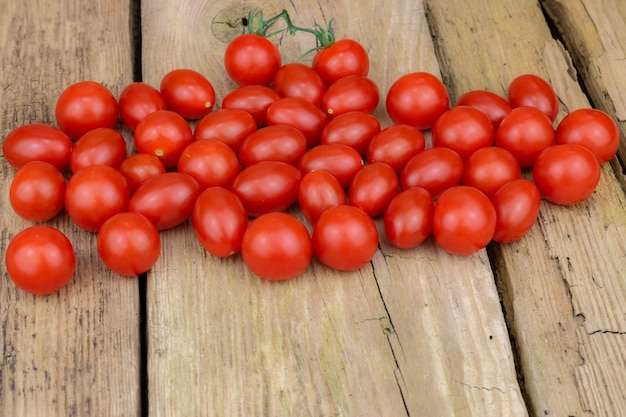 Piccoli pomodori rossi freschi su vecchie tavole di legno