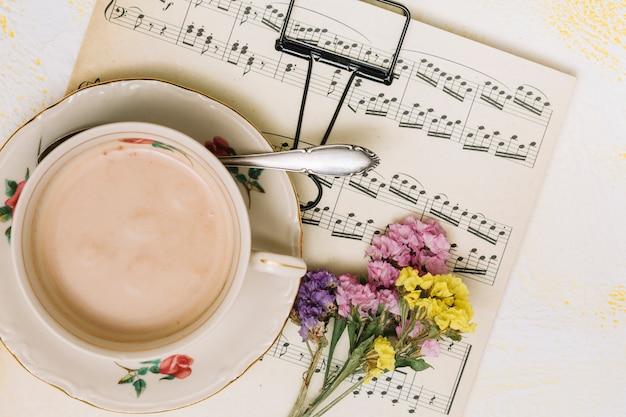 Piccoli rami di fiori con tazza di caffè sul foglio di musica