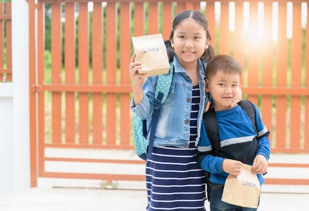 Piccoli studenti che tengono la borsa del pranzo prima di andare a scuola