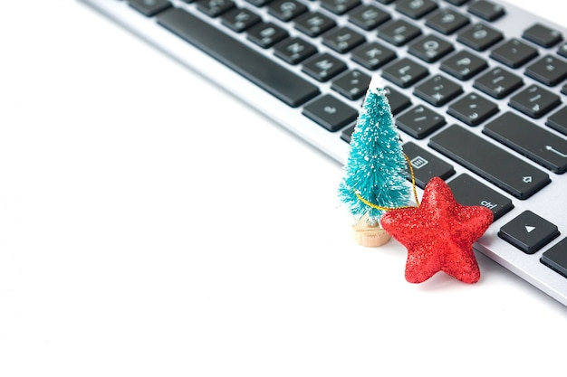Piccolo abete e stella rossa vicino alla tastiera di computer. atmosfera natalizia sul posto di lavoro.