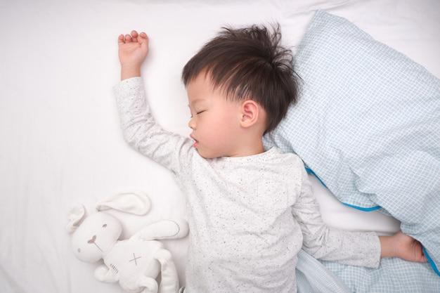 Piccolo asiatico sveglio 3 - 4 anni del ragazzo del bambino del bambino in pigiama che dorme / che fa un pisolino a letto, ora di andare a letto per il concetto dei bambini