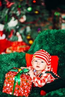 Piccolo bambino affascinante in camicia a quadri rossa e cappello di natale