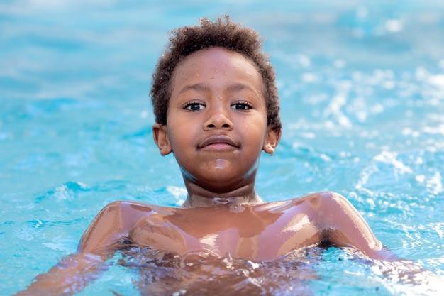 Piccolo bambino africano che spruzza fuori nello stagno