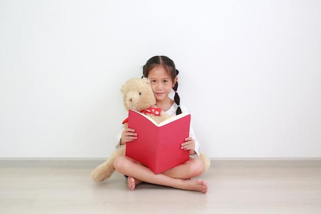 Piccolo bambino asiatico sveglio che legge un libro, abbracciando un orsacchiotto