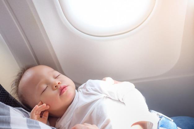 Piccolo bambino asiatico sveglio del bambino del bambino di 18 mesi / 1 anno che dorme sull'aeroplano con lo spazio della copia