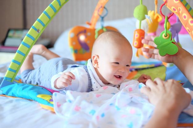 Piccolo bambino asiatico sveglio del neonato di 5 - 6 mesi al tempo della pancia