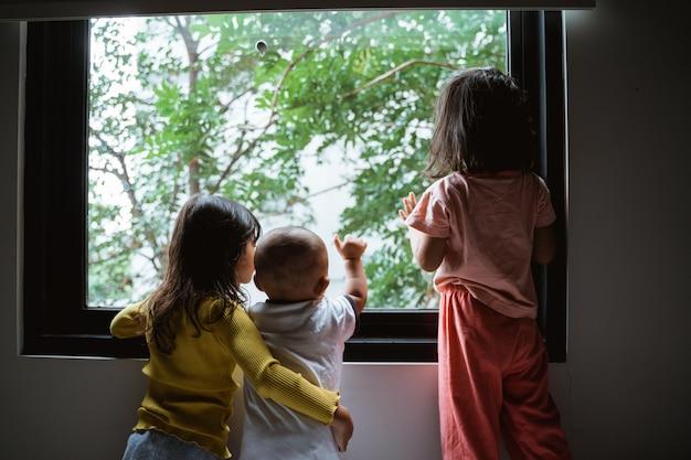Piccolo bambino asiatico tre che vede dal vetro di finestra