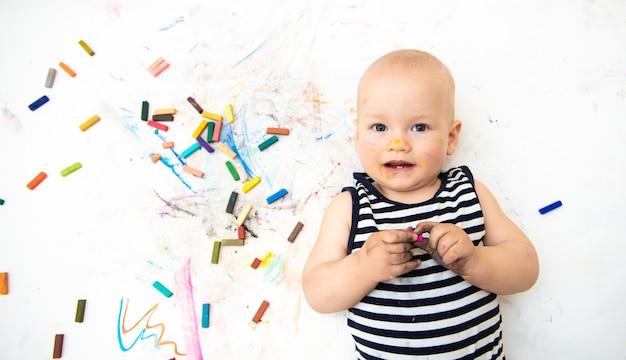 Piccolo bambino carino con creatività disegna con i pastelli a casa su un foglio di carta bianca. il concetto di sviluppo precoce della creatività da parte dei bambini