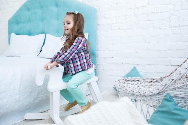 Piccolo bambino cavalca cavallo bianco in legno in camera blu