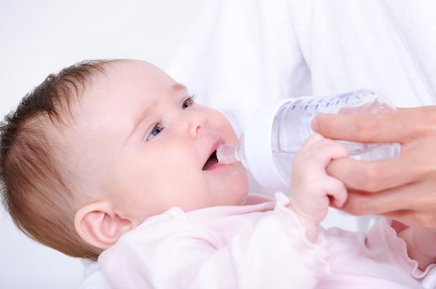 Piccolo bambino che beve latte dalla bottiglia