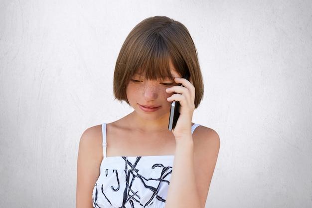 Piccolo bambino che comunica tramite smart phone con i suoi genitori mentre guarda in basso.
