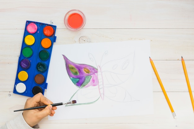 Piccolo bambino che dipinge una farfalla sulla pagina bianca con acquerello