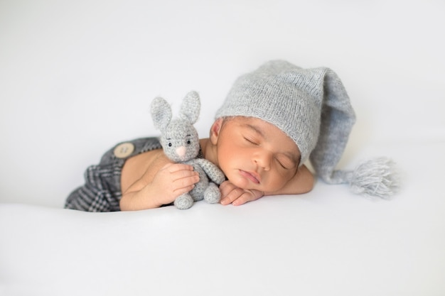Piccolo bambino che dorme con cappello grigio carino e con coniglio giocattolo nelle sue mani