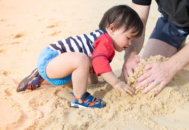 Piccolo bambino che gioca a sabbia con i genitori sulla spiaggia in vacanza estiva