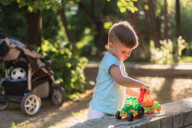Piccolo bambino che gioca con i giocattoli nel parco un giorno soleggiato