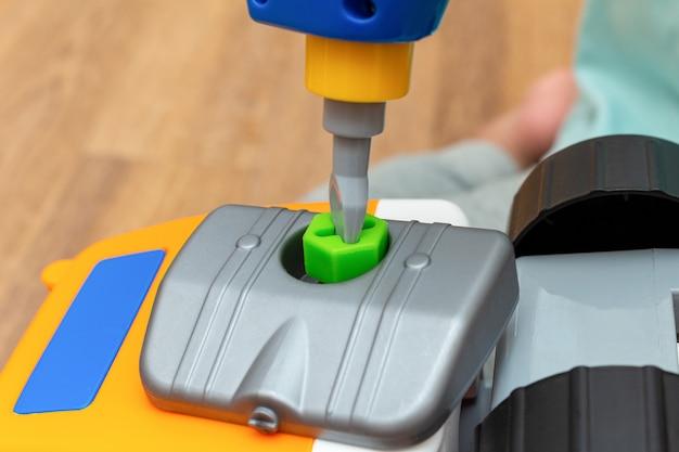 Piccolo bambino che gioca con la fine del trattore del costruttore del giocattolo su