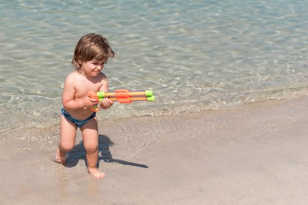 Piccolo bambino che gioca con la pistola ad acqua in spiaggia