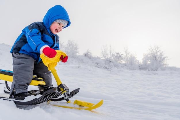 Piccolo bambino che guida un motorino di neve in inverno