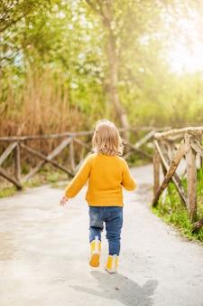 Piccolo bambino che indossa stivali da pioggia gialli, camminando nel bosco