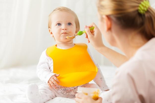 Piccolo bambino che si alimenta con un cucchiaio