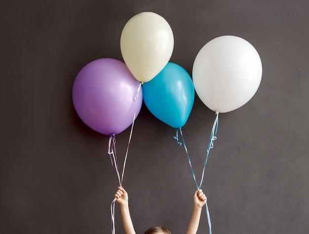 Piccolo bambino che tiene palloncini colorati