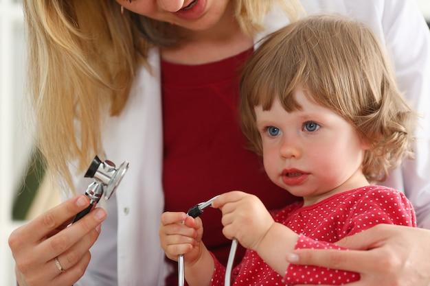 Piccolo bambino con stetoscopio alla reception del medico.