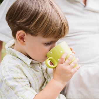 Piccolo bambino del primo piano che beve tè