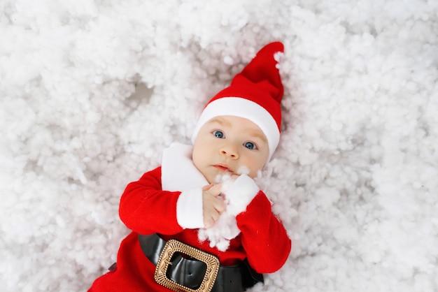 Piccolo bambino della santa che si trova sulla sua schiena in neve artificiale, regalo di natale